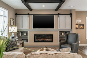 Exposed beam ceiling with sliding barn door entertainment center & fireplace.